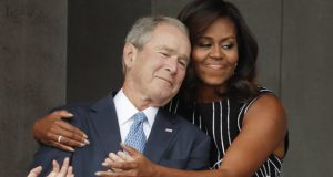 Former President George W. Bush and First Lady Michelle Obama sharing a hug at the opening of the National Museum of African American History and Culture